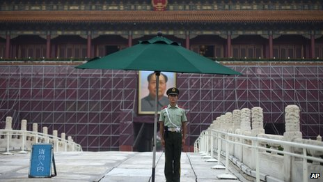 A paramilitary policeman guards his post in front of Tiananmen Gate, surrounded by scaffolding for repainting work ahead of the 1 October National Day in Beijing, 28 August 2013