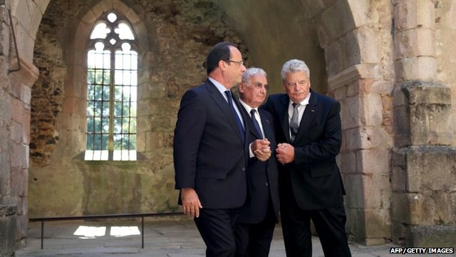 French president Francois Hollande and his German counterpart Joachim Gauck hold hands in the ruins of the church of Oradour-sur-Glane with Robert Hebras, 88, one of the last survivors of the World War II massacre
