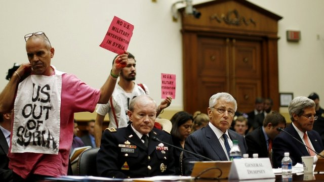 Protesters stand behind (from left) Chairman of the Joint Chiefs of Staff General Martin Dempsey, US Defence Secretary Chuck Hagel, and US Secretary of State John Kerry