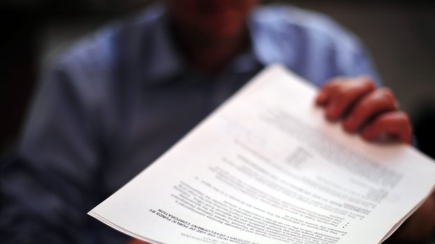 Reporter reads a copy of the leaked  Department for Communities and Local Government report