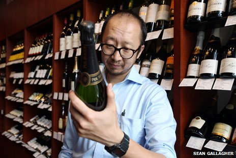 Hector Jiang, assistant shop manager of the Pudao Wines store in central Beijing, inspects a bottle of wine. China. Friday 19 July, 2013