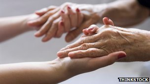 Carer and patient hold hands