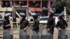 Egyptian security officers guard the scene of a bomb attack