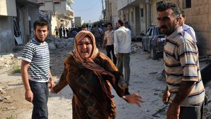 A Syrian woman runs through the debris after an air strike
