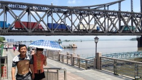 Trucks drive along a bridge connecting Dandong, China with North Korea