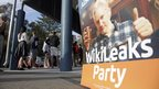 A placard showing WikiLeaks founder Julian Assange is set up as voters line up to fill in their ballots at a polling booth at Bondi Beach in Sydney, Saturday, 7 September