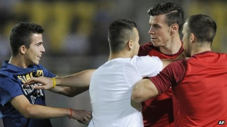 Gareth Bale is accosted by two fans during the World Cup qualifier in Skopje, Macedonia