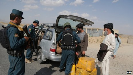 Afghan policemen search passengers at a checkpoint where Taliban militants kidnapped Fariba Ahmadi Kakar in Ghazni province on 14 on August 2013
