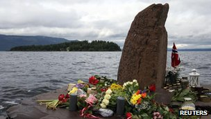 Flowers and candles are placed on the shore opposite to the Utoeya Island, Norway, Sunday, 24 July, 2011