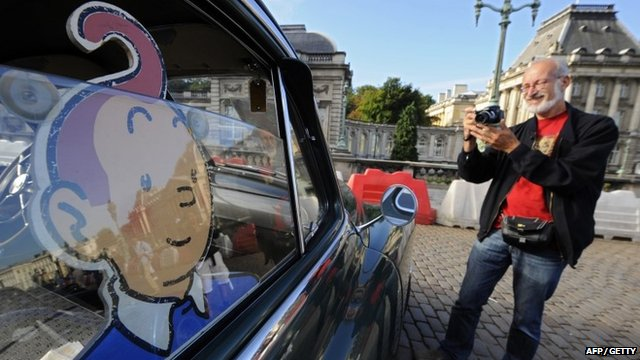"A man takes a picture of a vehicle of ""Tintin magazine"" car rally on September 8, 2013 in Brussels."