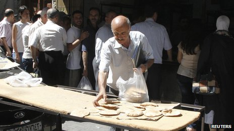 File picture of Syrians waiting in line to buy bread at al-Shaalan market in Damascus (28 August 2013)