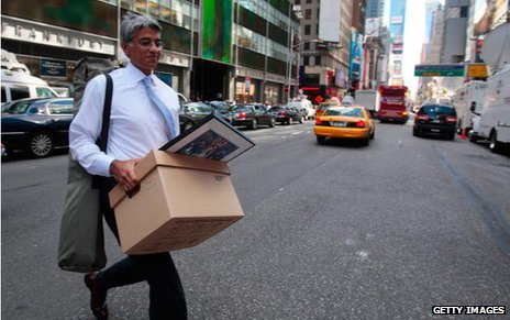 Lehman employees carries a box of belongings