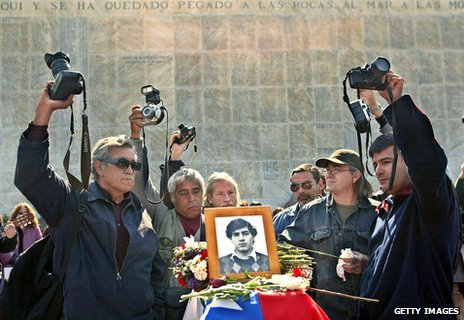 Mourners and photographers around the coffin of Rodrigo Rojas Denegri as his body was relocated in 2003