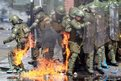 A riot policeman catches fire