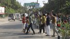 In this Saturday, Sept. 7, 2013 photograph, an unidentified group shouts slogans as Indian security forces arrive to quell communal clashes in Muzaffarnagar district, India