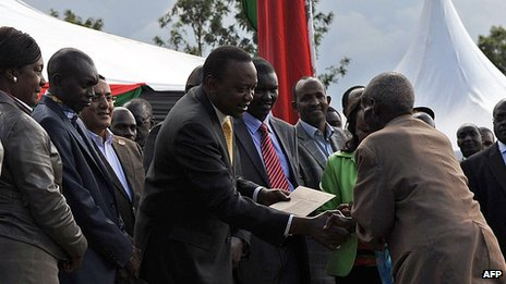Kenya's President, Uhuru Kenyatta, and his deputy, William Ruto, hand out cheques  on September 7, 2013 at Eldoret in Kenya's North-Rift