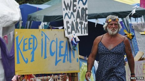 A man wearing a dress walks past signs at the protest camp