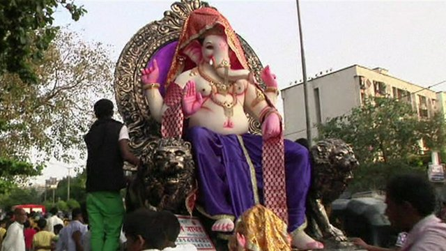 A statue of Lord Ganesh is paraded through the streets