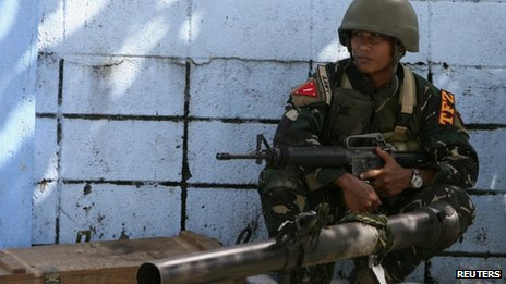 A government soldier squats next to a 90RR shoulder-fired rocket launcher while awaiting orders after Muslim rebels members of the Moro National Liberation Front (MNLF) occupied villages in Zamboanga city, southern Philippines, 9 September 2013