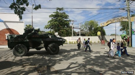 Residents walk past a government military vehicle as they evacuate near an area where members of Muslim rebels Moro National Liberation Front (MNLF) have occupied in Zamboanga city, southern Philippines, 9 September 2013