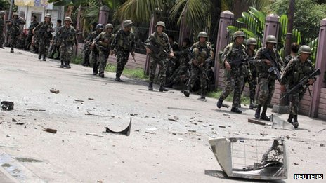 Security forces walks past debris scattered on a street after rebels from the Moro National Liberation Front (MNLF) clashed with government troops in Zamboanga city, southern Philippines, 9 September 2013