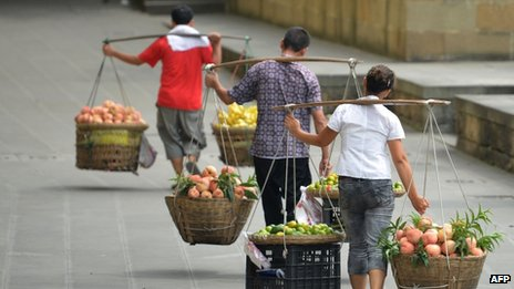 This picture taken on 8 August 2013 shows a vegetable vendors carrying their produce to sell in China's south-west metropolis of Chongqing