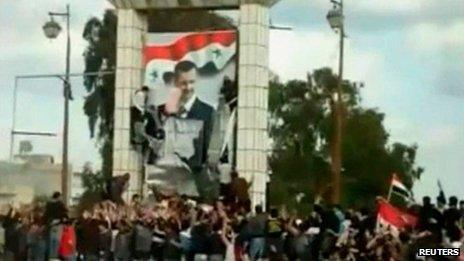 Protesters tear down a portrait of Bashar al-Assad in Deraa (March 2011)