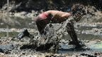 A boy takes part in a traditional mud surfing competition called Skylot, giving thanks for the sea harvest, in Lekok Village, East Java in Indonesia on 15 August