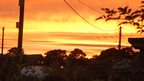 An orange, cloudy sky. In the foreground are trees, houses and telegraph poles and wires.