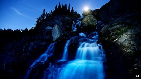The moon is seen over a waterfall near Logan Pass, Glacier National Park, Montana, on 25 July 2013