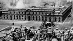 Chilean Army troops positioned on a rooftop fire on the La Moneda Palace in Santiago