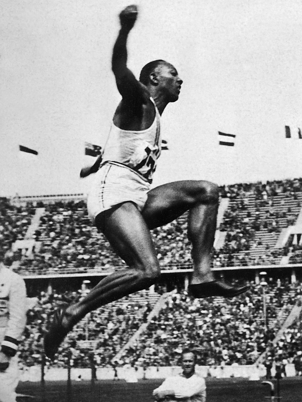 Jesse  Owens is airborne during the long jump event
