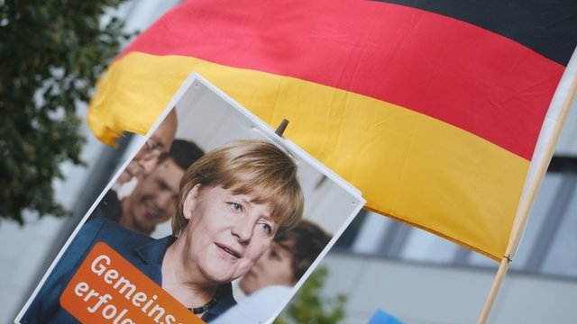 Angela Merkel supporters hold up a German flag and advertisement
