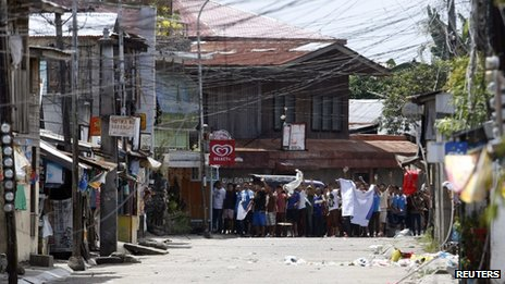 "Residents believed to be hostages and used as human shields of Moro National Liberation Front rebels wave white cloth and shout to the government soldiers to ""stop firing"" while standing in the rebels' positions in downtown Zamboanga city, in southern Philippines 11 September 2013"
