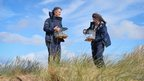 Wildlife experts hold their tanks of sand lizards