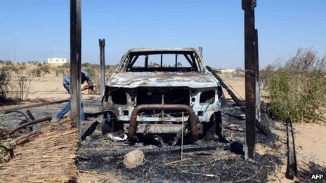 The wreckage of a burnt car is seen after assaults on militant targets by the Egyptian army, in a village near Sheikh Zuweid in Sinai