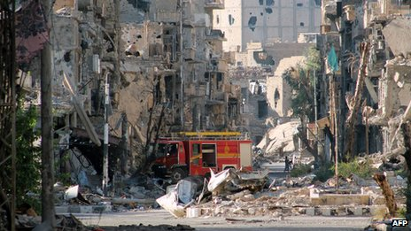 Fire engine left amid heavily damaged buildings in Syria's eastern town of Deir Ezzor on 10 September 2013