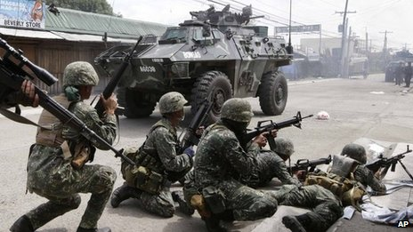 Government troopers aboard an Armoured Personnel Carrier fire at Muslim rebels in an operation to rescue scores of hostages being used as human shields by the rebels on the fourth straight day Thursday, 12 September 2013 at Zamboanga city in southern Philippines