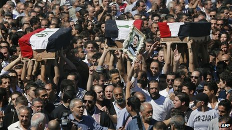 People carry the coffins of three Maaloula residents through the streets of Damascus (10 September 2013)