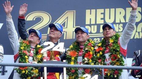 Drivers of the Audi R18 e-tron quattro gesture on the podium after winning the 90th edition Le Mans 24 hours endurance race