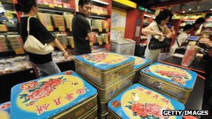 "Shoppers inspect boxes of ""mooncakes"""