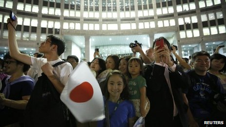 "Girl waves Japan's national flag as visitors take photos during an event titled ""Tokyo 2020 Host City Welcoming Ceremony"