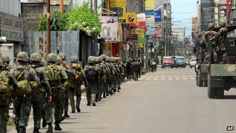 Government soldiers patrol a street as during heavy fighting between rebels and government forces as the stand-off enter its fourth day in Zamboanga city, in southern island of Mindanao, on 12 September 2013