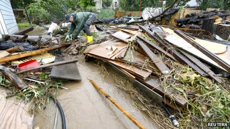 A man (requested his name not be used) tries to untangle debris that have been washed down to his home after severe flooding in Boulder, Colorado 12 September 2013