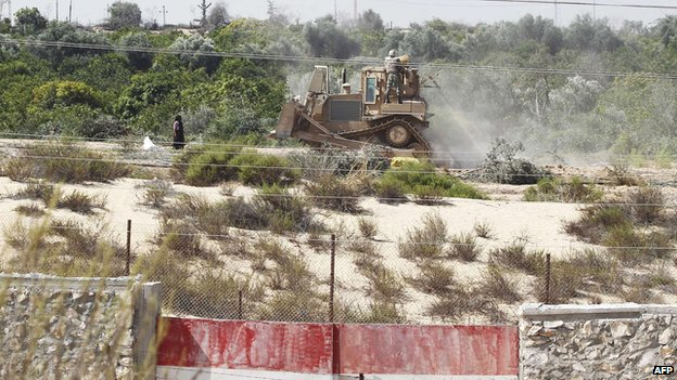 A picture taken from the southern Gaza Strip shows an Egyptian soldier standing on a bulldozer used to flatten fields near the border between Egypt and the Palestinian territory on 12 September 2013.