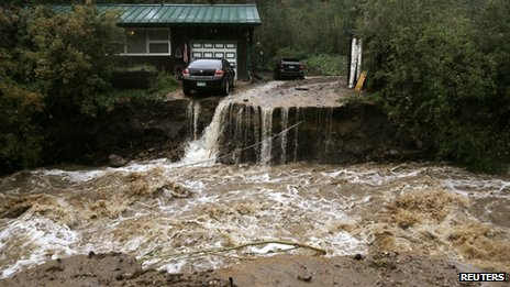 A home and car are stranded after a flash flood in Coal Creek destroyed the bridge near Golden, Colorado 12 September 2013