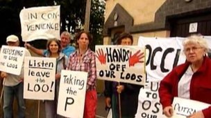 A crowd protests against the public toilets plan
