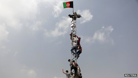 Afghan football fans climb an electrical pole to celebrate winning the South Asian Football Federation championship after their team defeated India during the final match, in Kabul on 12 September 2013.
