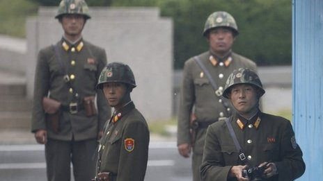 North Korean soldiers watch south at the truce village of Panmunjom in the demilitarized zone separating North Korea from South Korea, north of Seoul, 11 September 2013