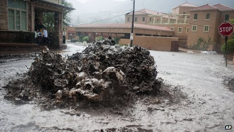 Floodwaters erupt out of a sewer on Canon Avenue in Manitou Springs, Colorado, on Thursday